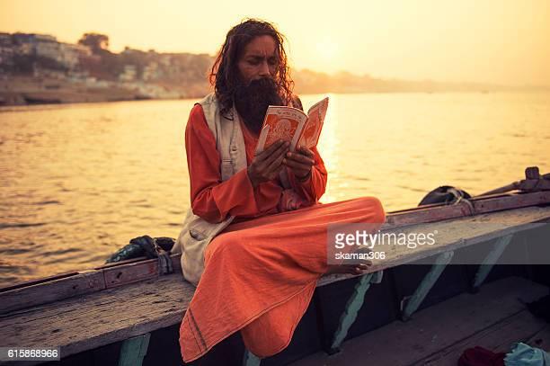 sadhu against the sun on the boat near Ganga river