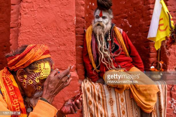 A sadhu applies paint on his face as another one looks at him near the Pashupatinath temple ahead of Hindu festival 'Maha Shivaratri' in Kathmandu on...