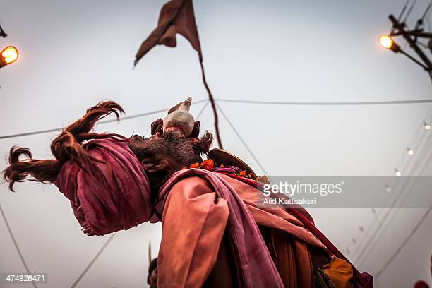 Sadhu blows a conch shell at the Sangam the confluence of Ganges Yamuna and mythical Saraswati rivers during Maha Kumbh Mela