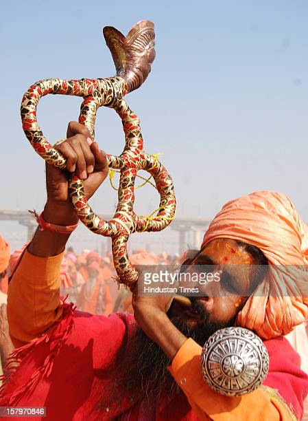 A sadhu blows the traditional bugle during the 'Dharam Dwaj Sthapna' ceremony that marks the setting up of their camp for the 56day Mahakumbh at...