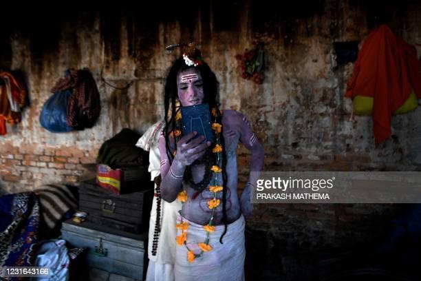 Sadhu dressed as God Lord Shiva looks at his reflection on a mirror during 'Maha Shivaratri' festival at Pashupatinath temple area in Kathmandu on...