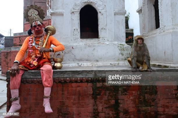 A sadhu dressed as Hanuman the Hindu monkey god looks on while sitting next to a macaque monkey at the Pashupatinath Temple area in Kathmandu on July...