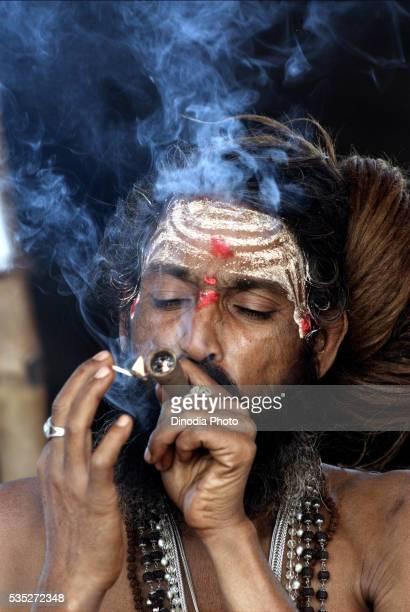 A sadhu from the Juna Akadha smoke opium at their camp during the Ardh Kumbh Mela at Allahabad, Uttar Pradesh, India.