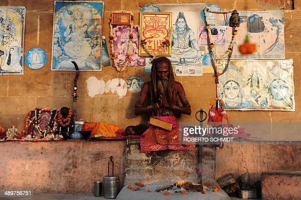 A Sadhu Hindu holy man prays at sunrise at one of the ghats on the banks of the river Ganges which is the holiest of rivers for hindus and is...