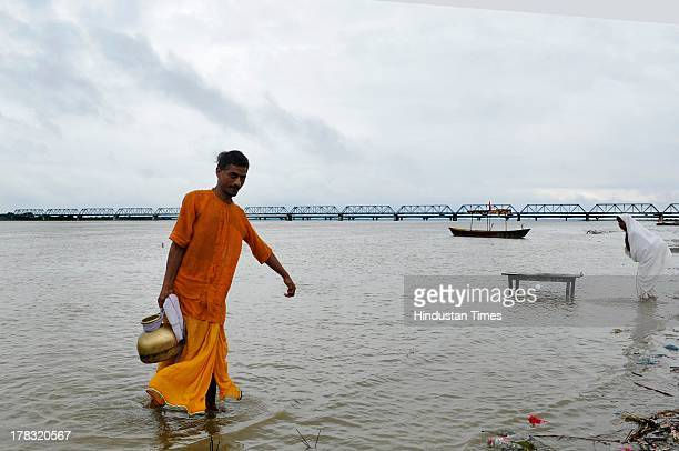 Sadhu holds a container which he filled with holy water at Saryu Ghat on August 28, 2013 in Ayodhya, India. Three days after Vishwa Hindu Parishad...