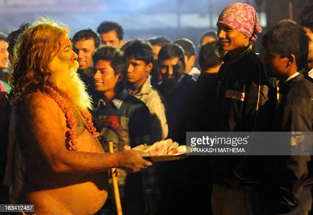 Sadhu holds a plate near the Pashupatinath Temple on the eve of the Hindu festival Maha Shivaratri in Kathmandu on March 9, 2013. Hindus mark the...