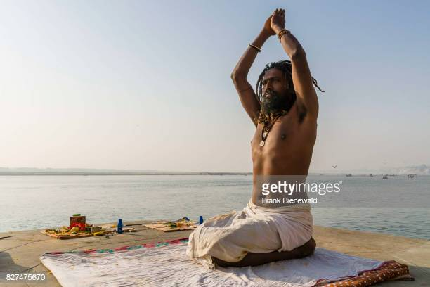 Sadhu holy man is practising yoga asana on a platform at the holy river Ganges at Meer Ghat in the suburb Godowlia