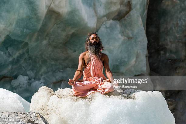 Sadhu holy man is sitting and meditating in lotus pose padmasana on a block of ice at Gaumukh the main source of the holy river Ganges