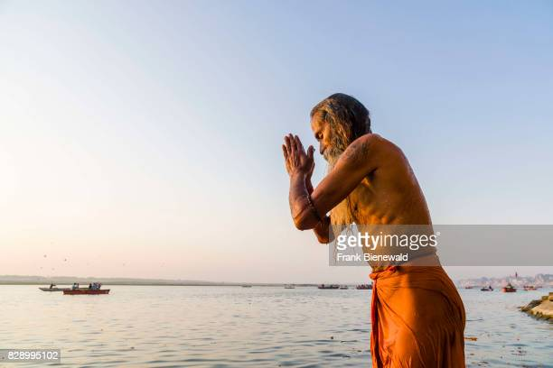 Sadhu holy man is standing in the water of the holy river Ganges and praying at Lalita Ghat in the suburb Godowlia