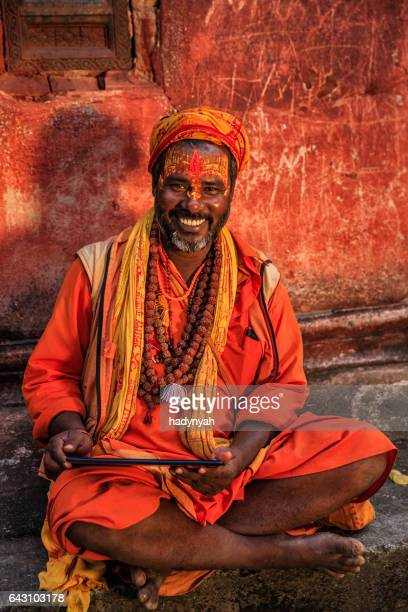 Sadhu - indian holyman using digital tablet