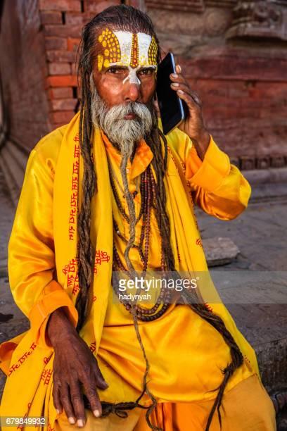 Sadhu - indian holyman using mobile phone