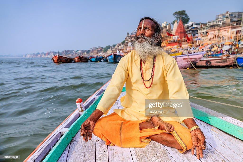 Sadhu is meditating in boat on Holy Ganges River, Varanasi : Stock Photo