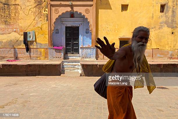 CONTENT] Sadhu making a greeting sign by a colorful yellow house in the streets of Vrindavan Uttar Pradesh India