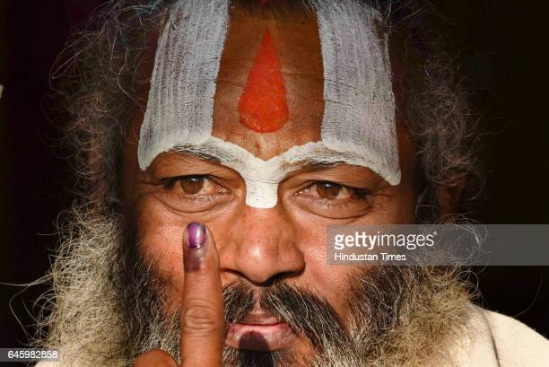 Sadhu or a holy man shows his inked finger after casting his vote at a polling booth during the 5th phase of Parliamentary election on February 27...