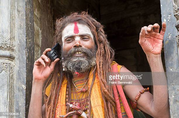 Sadhu or Holy Man using his mobile phone opposite the burning ghats near Pashupatinath Temple