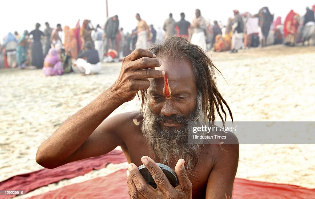 A sadhu prepare in the morning after taking bath at the bank of Sangam confluence of river Ganga, Yamnuna and mythical Saraswati on the occasion of Makar Sankranti on January 15, 2013 in Allahabad, India. Kumbh is World's biggest religious gathering, in which more than 100 million of Hindus and sikh devotees will take part over next 55 days. Apart from being pilgrimage of faith, salvation and hope for millions of devotees, it also serve as meeting ground for the vast spectrum of Indian religious and spiritual views.
