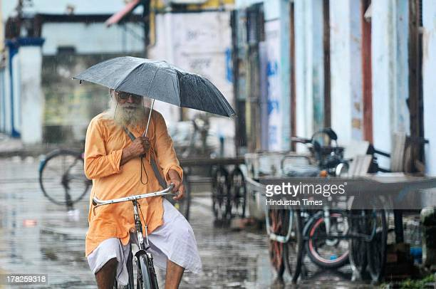 A sadhu rides his bicyle during rainfall on August 27 2013 in Ayodhya IndiaTwo days after the failed Parikarma attempt by Vishwa Hindu Parishad...