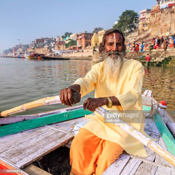 sadhu rowing boat on the holy ganges river in varanasi - ghat stock pictures, royalty-free photos & images