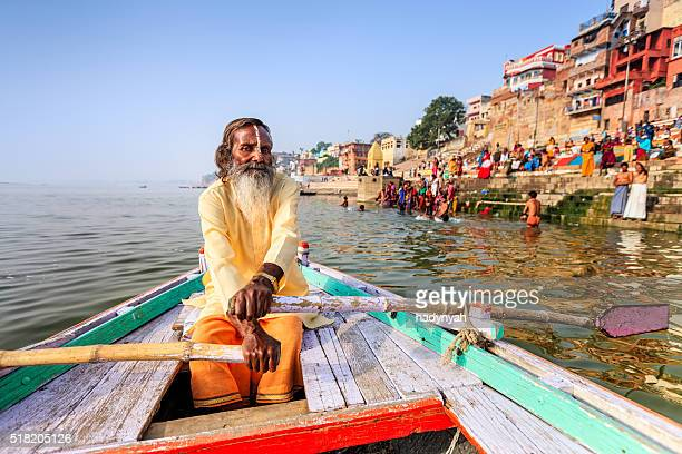 sadhu rowing boat on the holy ganges river in varanasi - varanasi stock pictures, royalty-free photos & images
