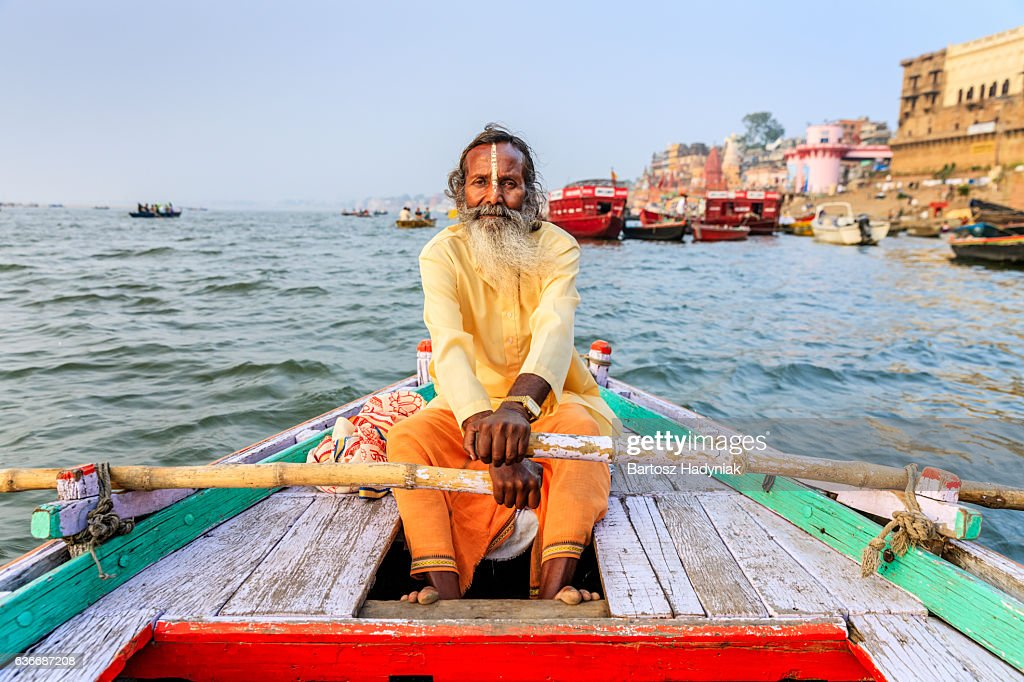 Sadhu rowing boat on the holy Ganges River in Varanasi : Stock Photo