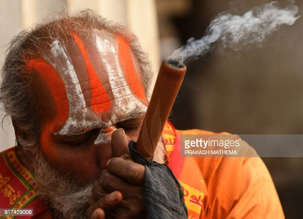 A Sadhu smokes a chillum a traditional clay pipe as a holy offering to Lord Shiva the Hindu god of creation and destruction near the Pashupatinath...