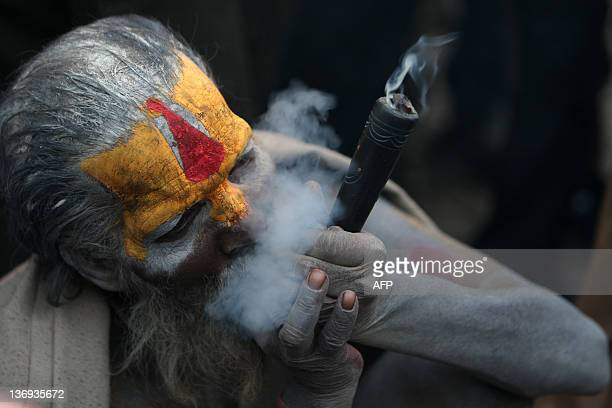 A Sadhu smokes ganja in a chillum as a holy offering from lord Shiva Hindu god of creation and destruction at the Pashupatinath temple during the...