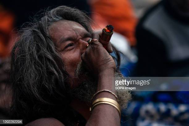 Sadhu smokes marijuana using a chillum as a holy offering during the festival at Pasupatinath Temple in Kathmandu Maha Shivaratri is a Hindu festival...