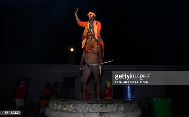Sadhu stands on a staff held up by a second Sadhu near the Pashupatinath Temple on the eve of the Hindu festival Maha Shivaratri in Kathmandu on...