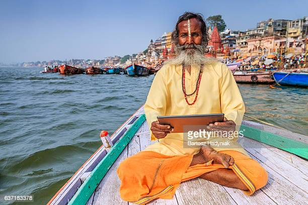 Sadhu using digital tablet in boat, Holy Ganges River, Varanasi