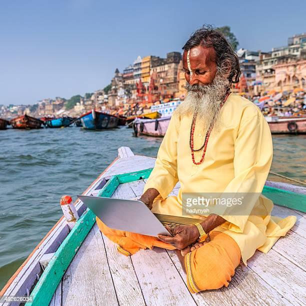 Sadhu, benutzt einen laptop in einem Boot auf den heiligen Ganges, Varanasi
