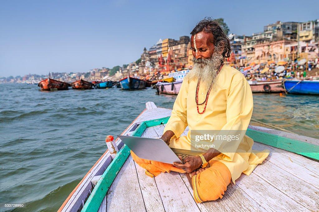 Sadhu utilizzando un computer portatile in barca sul Fiume Gange, sacra di Varanasi : Foto stock