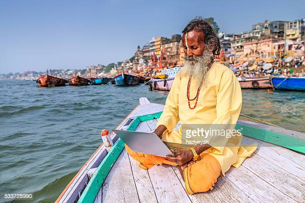 Sadhu using laptop in boat on Holy Ganges River, Varanasi