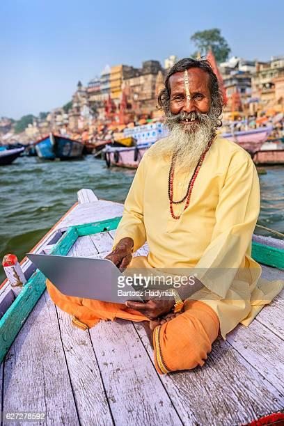 Sadhu à l'aide d'ordinateur portable en bateau sur le Fleuve Gange, sacrée de Varanasi