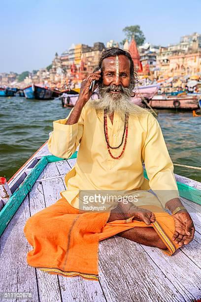 Sadhu à l'aide de portable en bateau sur la rivière sacré Gange, Varanasi