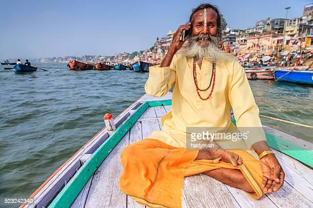 Sadhu using mobile in boat on Holy Ganges River, Varanasi