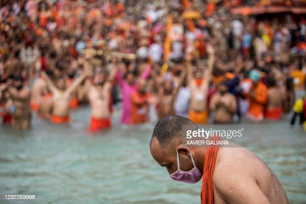 Sadhu wearing a facemask takes a holy dip in the Ganges river during the ongoing religious Kumbh Mela festival in Haridwar on April 12, 2021.