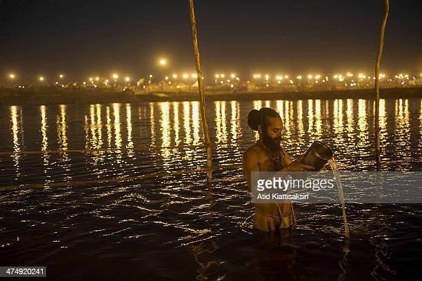 Sadhus bathe at night in the Ganges river at the Sangam, the confluence of Ganges, Yamuna and mythical Saraswati rivers during Maha Kumbh Mela.