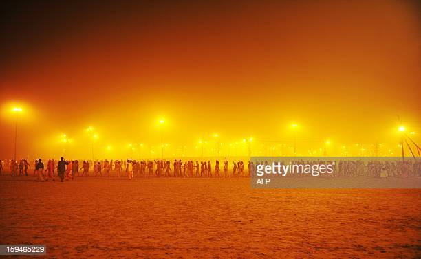 Sadhus or holy men walk in a procession towards the Sangham or the confluence of the the Yamuna and Ganges rivers to bathe before sunrise during the...