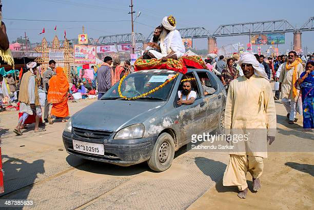 Sadhus roam around the Kumh mela ground atop a car. Kumbh Mela is a site of mass pilgrimage in which Hindus gather at a sacred river for a holy dip....