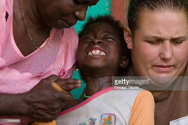 Sadia Mesuna center cries while having a Guinea worm extracted at the Carter Center's containment center in Savelugu Village in northern Ghana...