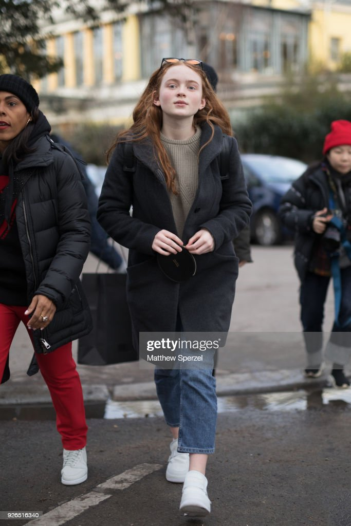 Sadie Sink is seen on the street attending Undercover during Paris Fashion Week Women's A/W 2018 Collection wearing a grey wool coat, sweater, and blue jeans with white sneakers on March 2, 2018 in Paris, France.