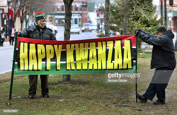 Sadiki Kambon left and his friend Tim Pitts secured the Happy Kwanzaa sign in the middle of Blue Hill Avenue in Grove Hall