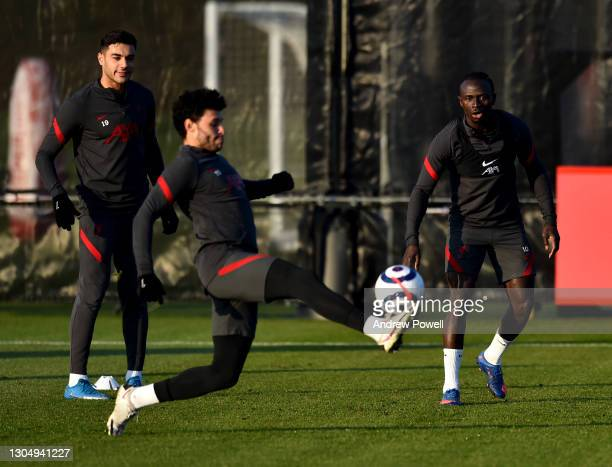 Sadio Mane and Ozan Kabak watching Alex Oxlade-Chamberlain of Liverpool during a training session at AXA Training Centre on March 02, 2021 in Kirkby,...