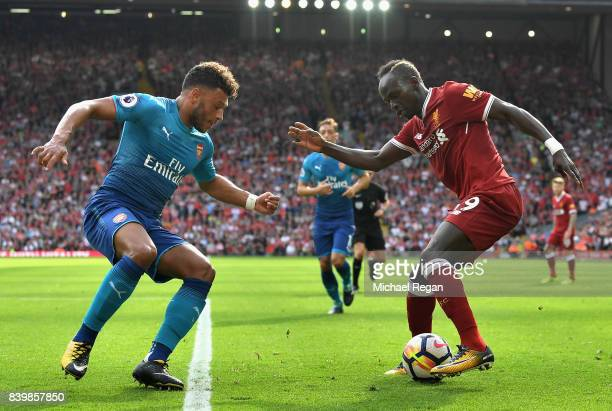 Sadio Mane of Liverpool and Alex OxladeChamberlain of Arsenal battle for possession during the Premier League match between Liverpool and Arsenal at...