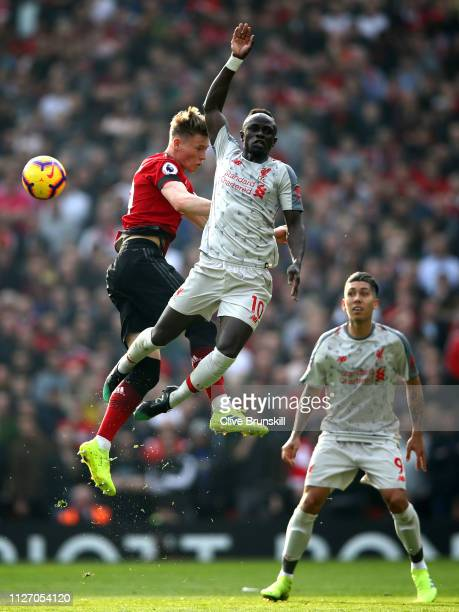 Sadio Mane of Liverpool battles for possession in the air with Scott McTominay of Manchester United during the Premier League match between...