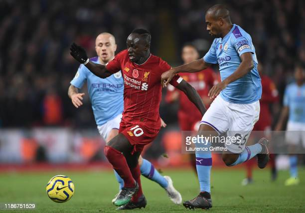 Sadio Mane of Liverpool battles for possession with Fernandinho of Manchester City during the Premier League match between Liverpool FC and...