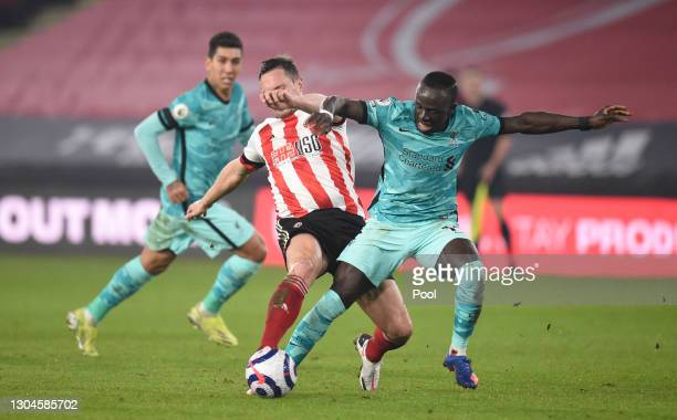 Sadio Mane of Liverpool battles for possession with Phil Jagielka of Sheffield United during the Premier League match between Sheffield United and...