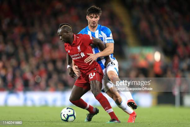 Sadio Mane of Liverpool battles with Christopher Schindler of Huddersfield during the Premier League match between Liverpool and Huddersfield Town at...