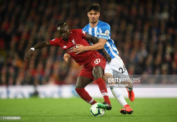 Sadio Mane of Liverpool battles with Christopher Schindler of Huddersfield Town during the Premier League match between Liverpool FC and Huddersfield...