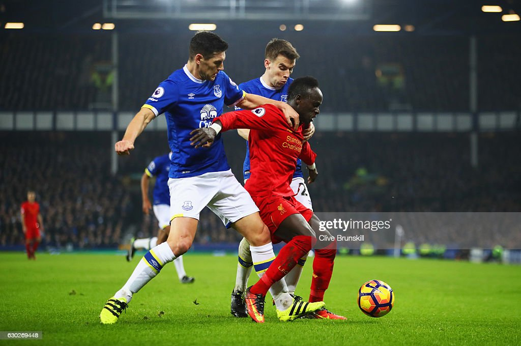 Sadio Mane of Liverpool battles with Gareth Barry and Seamus Coleman of Everton during the Premier League match between Everton and Liverpool at Goodison Park on December 19, 2016 in Liverpool, England.